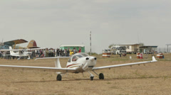 Aircraft with the running engine with the airshow visitors on the background Stock Footage