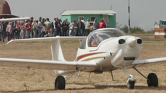Medium shot of an aircraft with the running engine with the airshow visitors on Stock Footage