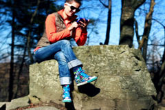 Happy woman texting on cellphone and sitting on rock in mountainous area Stock Footage