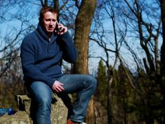 Happy man talking on cellphone and sitting on rock in the mountainous area Stock Footage