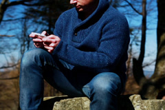 Man texting on the cellphone and sitting on the rock in the mountainous area Stock Footage