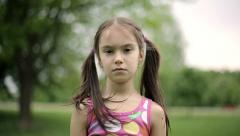 Portrait little girl is angry and disagrees crying in a summer park. Slow motion Stock Footage