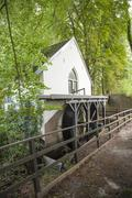 water mill with bladewheel in forest - stock photo