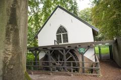 watermill with paddle wheel in forest - stock photo