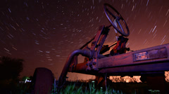 Circles of time  - timelapse old rusty tractor on star trails night - stock footage
