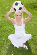 Smiling blonde holding a soccerball - stock photo