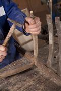 Carpenter repairing chair - stock photo