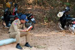 Cambodian policeman reads at angkor Stock Photos