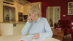 Senior woman pays bills by credit card over the phone Stock Footage