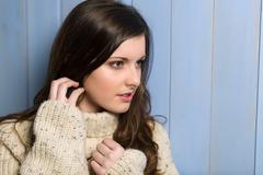 Brunette woman in beige sweater looking aside Stock Photos