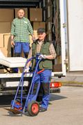 Mover two man loading furniture on truck Stock Photos