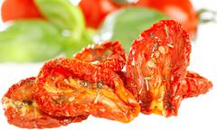 sun-dried tomatoes with basil leaves and tomato on background, o - stock photo
