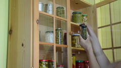 Girl from cupboards with glass takes two jars with capers garlic Stock Footage