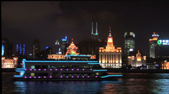 Sightseeing Boat on the Huang Pu River with the well lit Bund in Background at Stock Footage