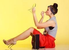 Cosmetic. pin-up girl woman with bun applying makeup on yellow. Stock Photos