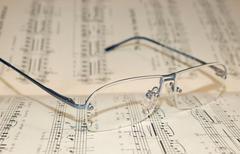 Glasses laying on score - stock photo