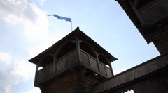 Wooden castle tower with a blue flag waving in the sky Stock Footage