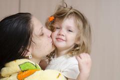 Mom hugs and kisses awakened fuzzy-looking child Stock Photos