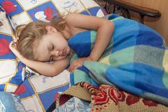child of four years sleep in a bed with an old sheets and blankets - stock photo