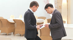 Stock Video Footage of business 5el S&A&D 077 two companions men discuss news on the tablet