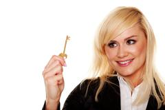 Successful woman holding brass key Stock Photos