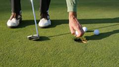 Close-up of golfer using putter to sink short putt Stock Footage