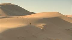 Berber man walking across the Sahara desert Stock Footage