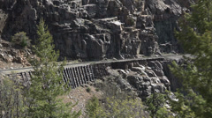 Steam engine railroad tracks steep cliff Colorado Rocky HD 120 Stock Footage