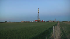Drilling Rig in Green Wheat Wide W Fence Stock Footage