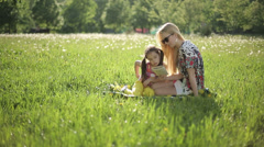 Mother and daughter sitting on the grass read book in summer park at sunset Stock Footage