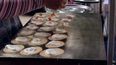 The making of Kanum Bueng (Coconut Crepes) by a Sidewalk Vendor Bangkok Stock Footage