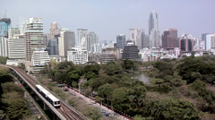 Skytrain with Lumphini Park and Skyline of Phloenchit and Sukhumvit District Stock Footage