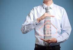 businessman banker holding home in hands - stock illustration