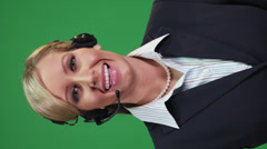A cheerful woman talking on a head set in front of a green screen Stock Footage