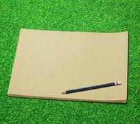 pencil and old blank sketch book on green grass background - stock photo