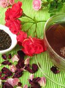 Black tea with rose flowers - stock photo