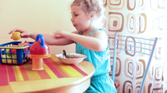 Child in blue dress eating gruel at the table and playing with her toys Stock Footage
