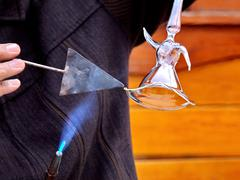 glass craftsman making a whirling dervish figure from molten glass - stock photo