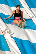 young woman enjoys going down slide in obstacle race - stock photo