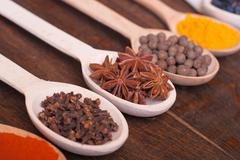 Background with spices ( turmeric , star anise , barberry , allspice , cloves ) Stock Photos