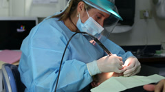 Dentist making a prophylaxis or a dental cleaning to a patient Stock Footage