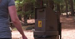 Female throwing away trash in park 4k Stock Footage