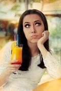 Bored Woman with Colorful Cocktail Drink Stock Photos