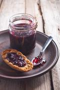 Black currant jam in glass jar and crackers Stock Photos