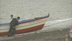 Men pulling in a traditional fishing boat Stock Footage