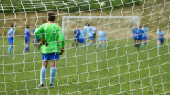 Children soccer game from behind goal net Stock Footage