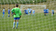 Stock Video Footage of Children soccer game from behind goal net