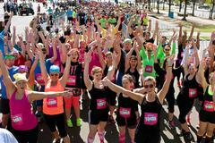 crowd of runners celebrates at start of obstacle course race - stock photo