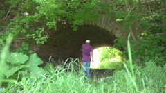 A man walks under an ancient old bridge Stock Footage