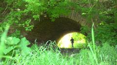 A man walks under an ancient old bridge Stock Footage
